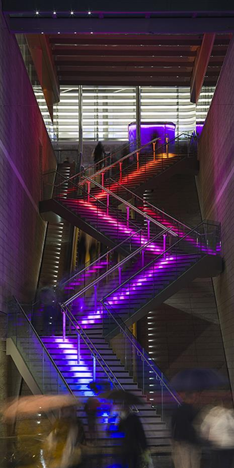 staircase ascending four storeys and lit up with LED light strip down the middle in red, purple, and blue