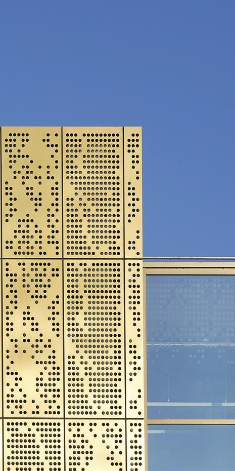 close up of copper alloy perforated facade and window