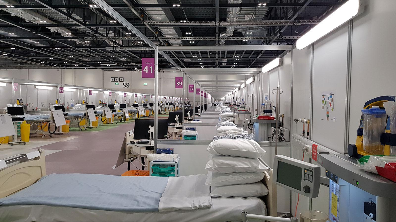 inside an NHS Nightingale Field Hospital set up inside a convention centre, showing rows of hospital beds and equipment bays