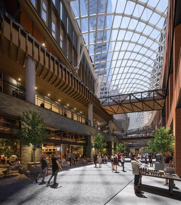 an indoor/outdoor retail promenade with three levels, connected by bridges, with warm neutral tones and brick and wood, all covered by a glazed canopy