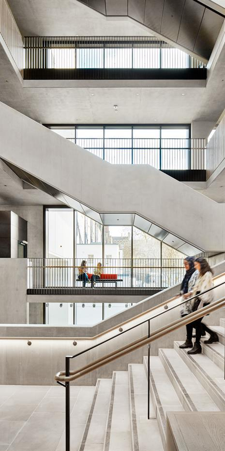 inside UCL Student Centre showing staircases and bridge walkways connecting various levels, all in soft polished concrete