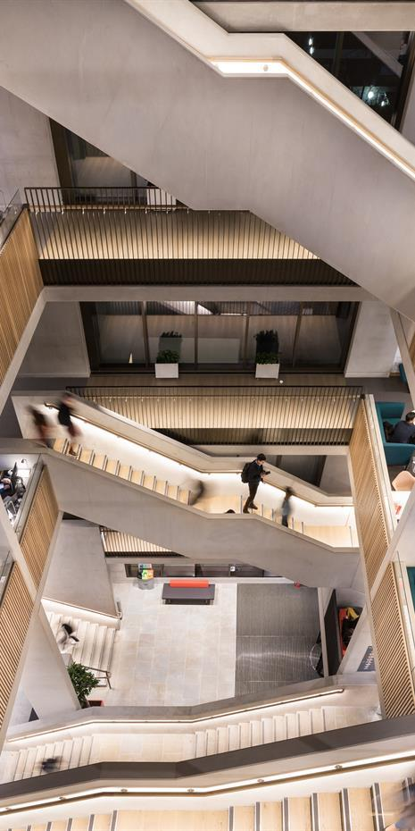 looking down an atrium / stairwell in UCL Student Centre showing many striking staircases and wooden cladding on the walls of each floor