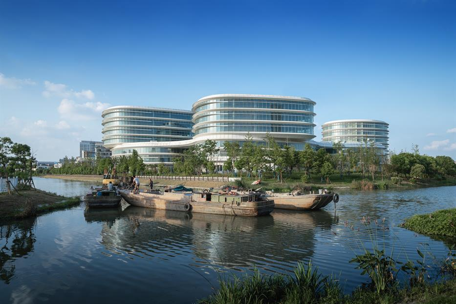 glazed office building with three visible volumes, with rounded oval shapes and curvilinear podium connection, all viewed from across a waterway with boats in the foreground