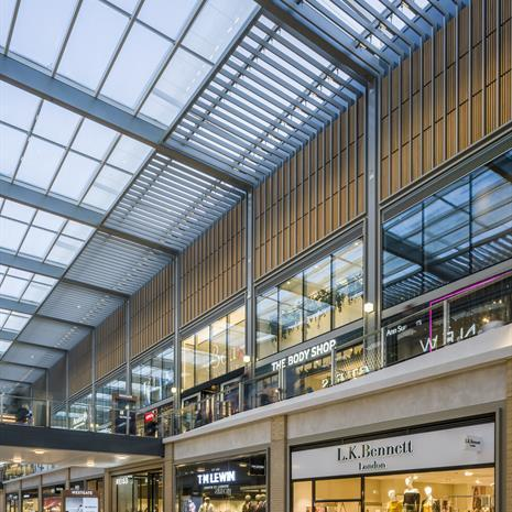 a covered exterior mall environment with glass overhead covering to protect from the elements, and two levels of retail storefronts