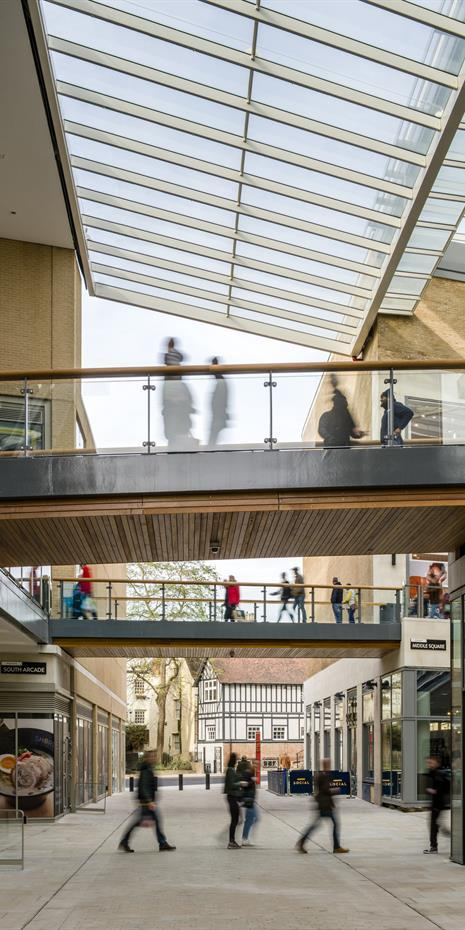 exterior retail promenade with two levels connected by bridges and glass canopy overhead