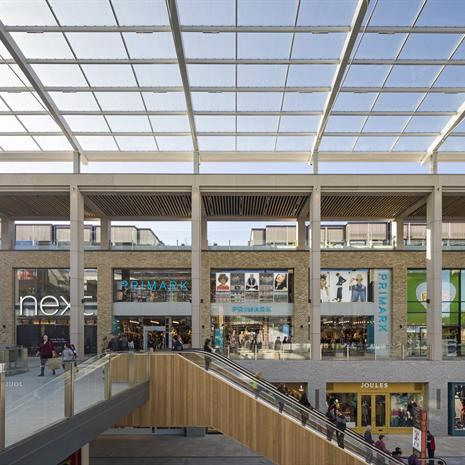 covered exterior mall environment with glass overhead covering and several levels of retail outlets