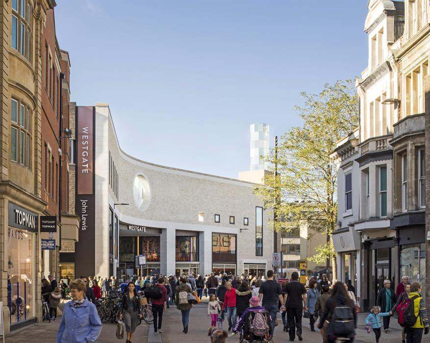 modern outdoor British high street pedestrian only boulevard with retail in a mix of historic building storefronts and new buildings