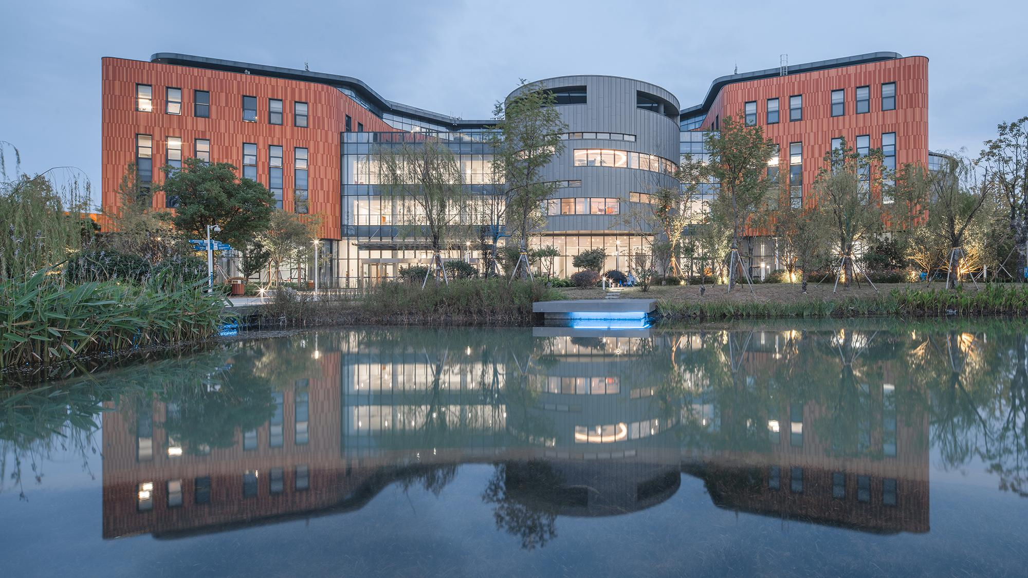 Xian Jiaotong Liverpool University viewed from the back from across a pond, showing a circular volume in the middle and wings of red brick cladding on either side